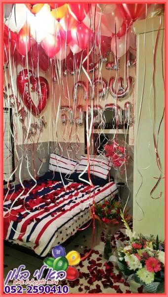 עיצוב מהמם ליום הנישואים כולל בלונים בחלל התקרה בלוני לבבות על הקיר כיתוב מבלונים, זרי פרחים, ועלי כותרת מפוזרים בחדר...